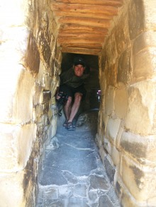 Morgan crawls through the tunnel exiting the Balcony House cave dwelling.