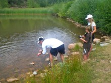 Morgan helps Colly and Kyle catch and release a trout from Down Valley Park near Placerville.
