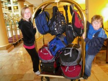 """Colly and Kyle with our luggage checking into the airport hotel tonight. We reduced our luggage to four packs for clothing, one small suitcase for our """"mobile office,"""" four carry-on backpacks, one camera bag and one purse."""